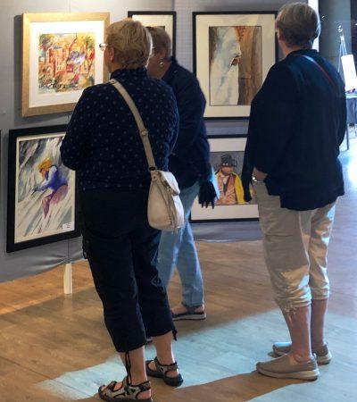 Ladies looking at watercolor art